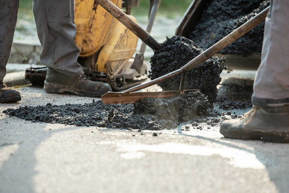 Two construction workers working together to patch a bump in the road with fresh asphalt.
